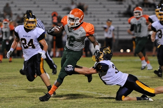 Mojave running back Ty Flanagan breaks away from Boulder City cornerback Sam Woodbury, right, and linebacker Jacob Jurgschot (24) last season. Flanagan leads the area in rushing with 649 yards. (D ...