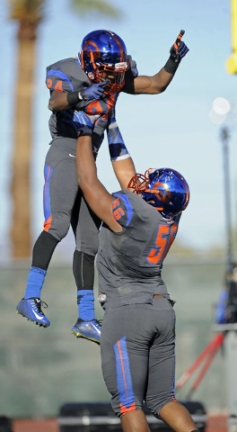 Bishop Gorman offensive guard Jackson Perry (56) hoists running back Russell Booze (24) after Booze scored a touchdown against Liberty in the Division I state football semifinal game at Rancho on  ...
