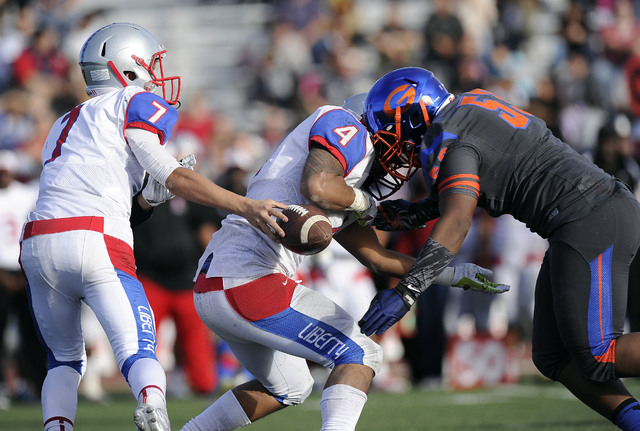 Bishop Gorman  linebacker Ferrall Hester (53) forces a fumble as Liberty quarterback Kenyon Oblad (7) hands off to running back Ethan Tuilagi (4) in the second half of the Division I state footbal ...