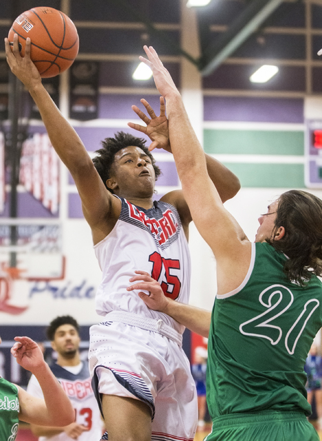 Liberty's Cameron Burist (15) drives to the basket over Green Valley's Canyon Lewis (21) during the Patriots home matchup with the Gators on Monday, Jan. 30, 2017, at Liberty High School, in Las V ...