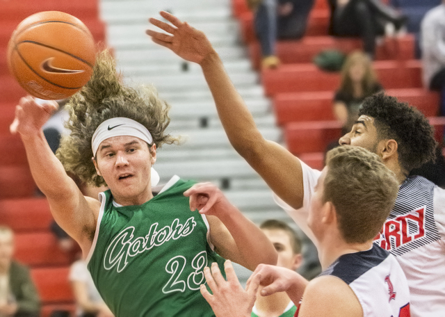 Green Valley's Matthew Tuttle (23) makes a wrap around pass past Liberty's Dyllan Robinson (13) during the Gators road matchup with the Patriots on Monday, Jan. 30, 2017, at Liberty High School, i ...