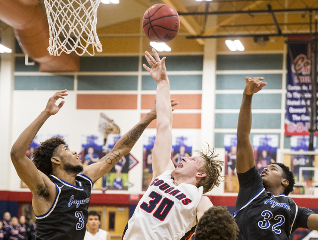 Coronado's Kennedy Koehler (30) fights for a rebound with Desert Pines' Trevon Abdullah-Booker (3) and Derrick Coleman (32) on Monday, Dec. 12, 2016, at Coronado High School, in Henderson. Benjami ...
