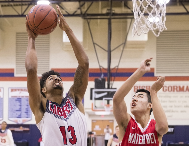 Liberty's Dyllan Robinson (13) shoots over Mater Dei's Michael Wang (23) during the Tarkanian Classic on Thursday, Dec. 15, 2016, at Bishop Gorman High School, in Las Vegas. Benjamin Hager/Las Veg ...