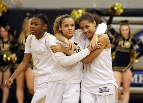 Essence Booker (center) and Kayla Harris share a hug during a game last season. (Ronda Churchill/Las Vegas Review-Journal)