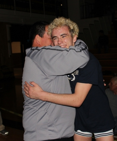 Shadow Ridge's Brendt Burleson (right) is hugged by coach Gus Gledhill after Burleson scored an upset win over Bishop Gorman's Mason Campbell in the 126-pound title match at the Sunset Regional at ...