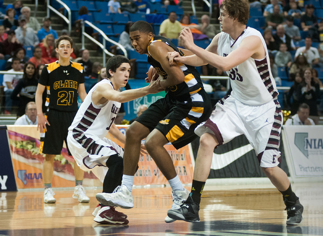 Clark's Sherron Wilson (35) tries to break through Elko's Eric Klekas (13) and Brian Pearson (35) during the Division I -A state final on Saturday.  Clark defeated Elko 43-25. (Kevin Clifford/Las  ...