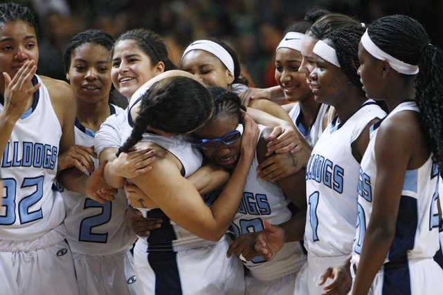 Tanjanae Wells (00) gets a hug as the Centennial girls basketball team celebrates its 65-52 win over Bishop Gorman in the Division I state championship game Friday, Feb. 27, 2015, at the Orleans A ...