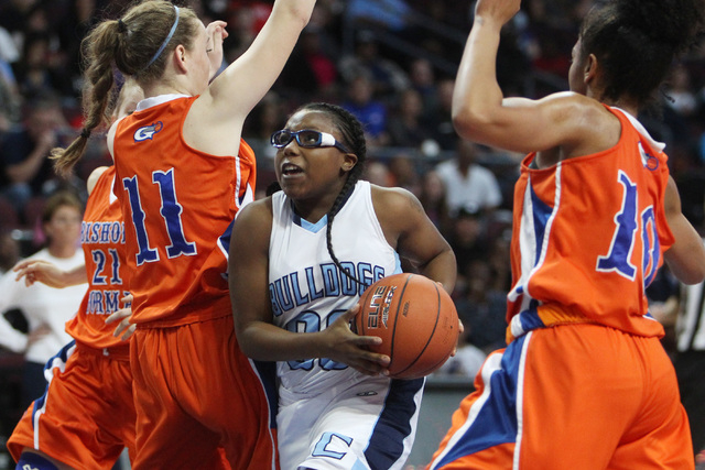 Centennial guard Tanjanae Wells drives to the basket between Bishop Gorman guard Madison Ulrey, left, and forward Alaysia Robinson during their Division I state championship game Friday, Feb. 27,  ...
