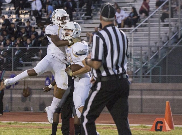 Faith Lutheran wide receiver Justin Taylor (81) celebrates with teammate Saundre Spiller (20) after scoring a first quarter touchdown during the Crusaders road matchup with the Skyhawks on Friday, ...