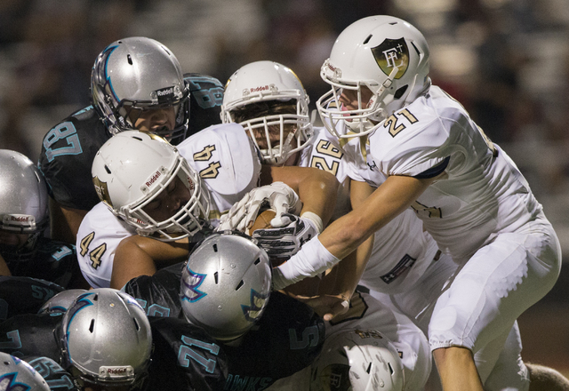 Silverado fullback Christopher-James Liana (5) is sandwiched between Faith Lutheran defenders Hunter Kaupiko (44), Blake Giuliani (26) and Alec Netski (21) during the Skyhawks home matchup with th ...