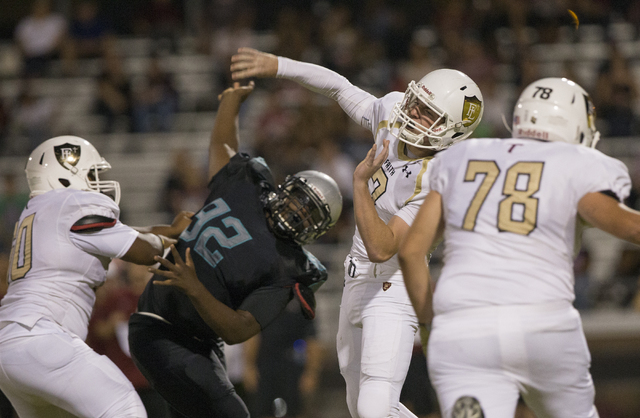 Faith Lutheran quarterback Sagan Gronauer (7) gets a pass off in traffic during the Crusaders road matchup with the Skyhawks on Friday, Sept. 16, 2016, at Silverado High School, in Las Vegas. Benj ...