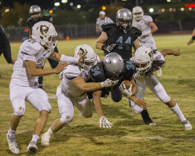 Silverado running back Keikiokalani Misipeka (34) is tackled by a group of Faith Lutheran defenders during the Skyhawks home matchup with the Faith Lutheran Crusaders on Friday, Sept. 16, 2016, at ...