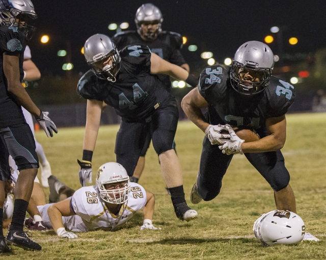 Silverado running back Keikiokalani Misipeka (34) avoids a loose helmet as he runs down the sideline during the Skyhawks home matchup with the Faith Lutheran Crusaders on Friday, Sept. 16, 2016, a ...