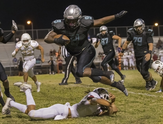 Silverado running back Nahzi Salih (9) leaps over a Faith Lutheran defender during the Skyhawks home matchup with the Crusaders on Friday, Sept. 16, 2016, at Silverado High School, in Las Vegas. B ...