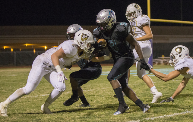 Silverado running back Nahzi Salih (9) fights for extra yardage with Faith Lutheran defenders during the Skyhawks home matchup with the Crusaders on Friday, Sept. 16, 2016, at Silverado High Schoo ...