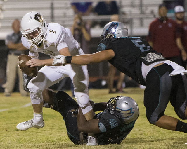 Faith Lutheran quarterback Sagan Gronauer (7) is sacked by Silverado defenders Christopher-James Liana (5) and Myron Mingo (41) during the Crusaders road matchup with the Skyhawks on Friday, Sept. ...