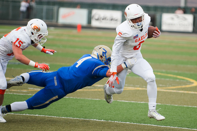 Bishop Gorman's Austin Arnold (6) breaks a tackle from Reed's Dylan Morell (4) on his way to a 37-yard touchdown reception in the Division I state championship game on Saturday in Reno. Gorman won ...