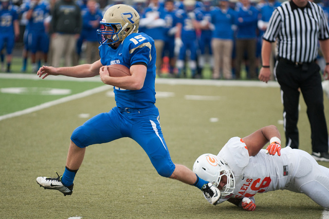Reed's Matt Denn (15) breaks a tackle from Bishop Gorman's Haskell Garrett (16) during the first half of the Division I championship game at Damonte Ranch on Saturday. Denn rushed for 82 yards and ...