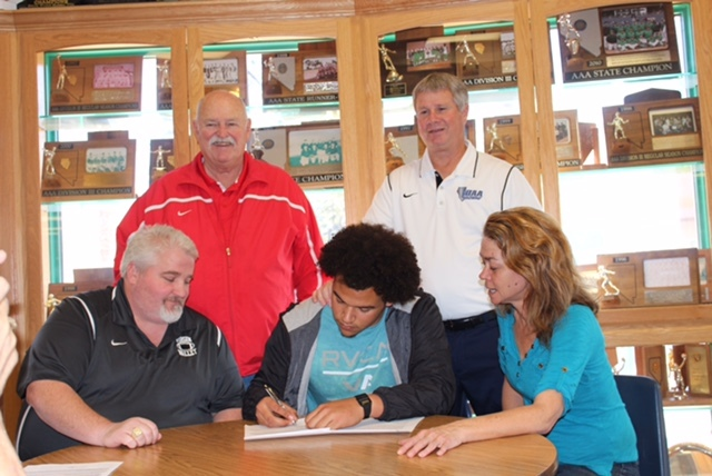 Virgin Valley's Chase Henderson signs a letter of intent to play football at Eastern Arizona. Henderson is surrounded by Virgin Valley head coach Yori Ludvigson, left, and his mother, Kimberly. As ...