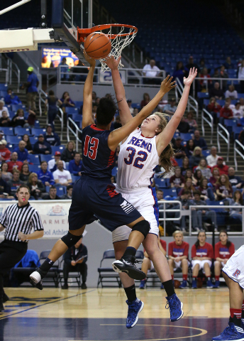 Reno's Morgan McGwire blocks a shot by Liberty's Aubre' Fortner during the Division I championship game in the NIAA basketball state tournament at Lawlor Events Center, in Reno, Nev., on Friday, F ...