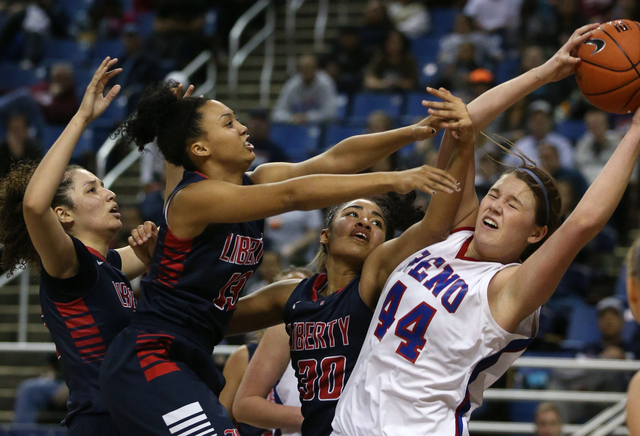 From left, Liberty Patriots Jazmin O'Bannon, Aubre' Fortner and Paris Strawther fight for a rebound with Reno's Mallory McGwire during the Division I championship game in the NIAA basketball state ...