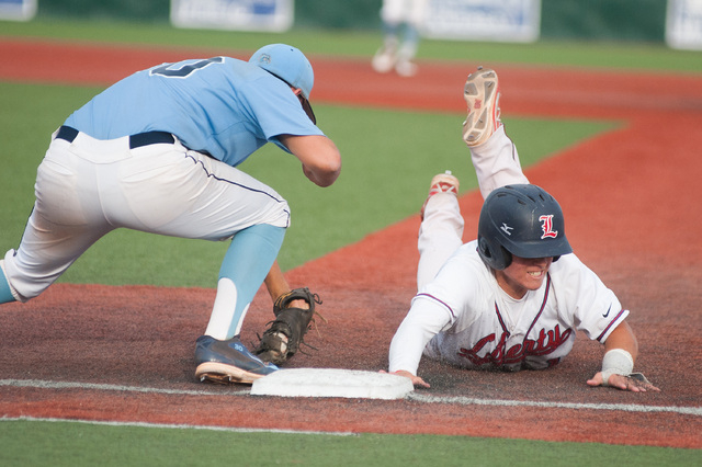 Liberty's Josh McCollum dives back to first base while Centennial's Travis Stevens attempts a tag on Friday in the Division I state tournament. Liberty won 3-2 to advance to Saturday's championshi ...