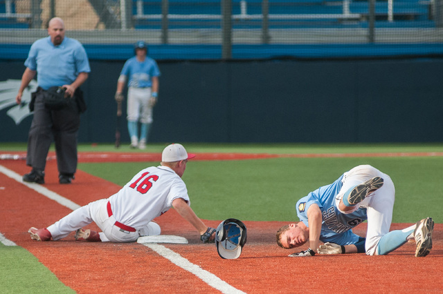 Liberty's Justin Lutes collides with Centennial's Jared Drizin at first base in the Division I state baseball semifinals on Friday. Lutes tagged Drizin out on the play, and Liberty won 3-2 to adva ...