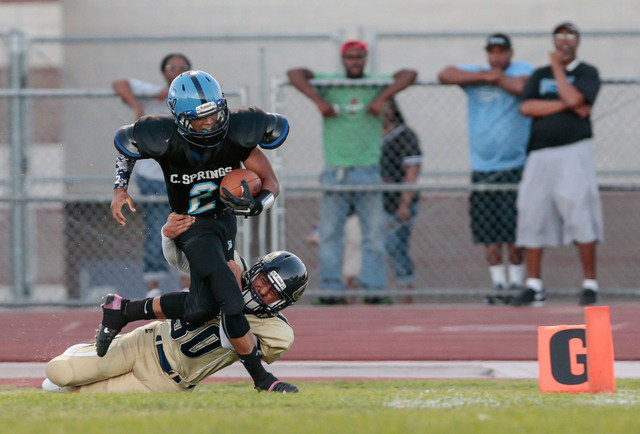 Canyon Springs junior Diamante Burton (2) attempts to break a tackle by Cheyenne senior Joseph Kunicki (30) while on his way to the goal line during a matchup at Canyon Springs High School, 350 Ea ...