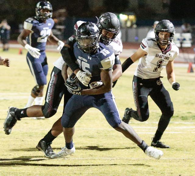 Shadow Ridge senior Malik Lindsey (15) moves the ball while Cimarron-Memorial junior Jonah La'ulu (54) attempts to bring him down during a football matchup at Shadow Ridge High School in Las Vegas ...