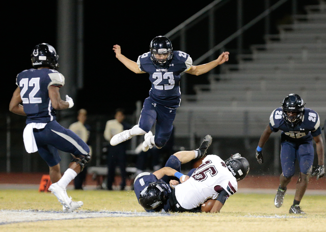 Shadow Ridge junior Sergio Martinez (23) leaps up to avoid players below him during a football matchup against Cimarron-Memorial held at Shadow Ridge High School  in Las Vegas, Friday, Oct. 7, 201 ...