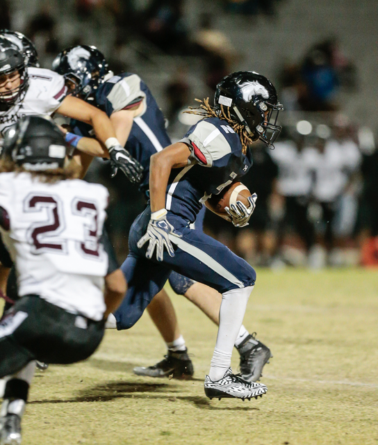 Shadow Ridge junior Elisha Young (2) breaks out and away from defenders while returning a kicked ball from Cimarron-Memorial during a football matchup held at Shadow Ridge High School in Las Vegas ...