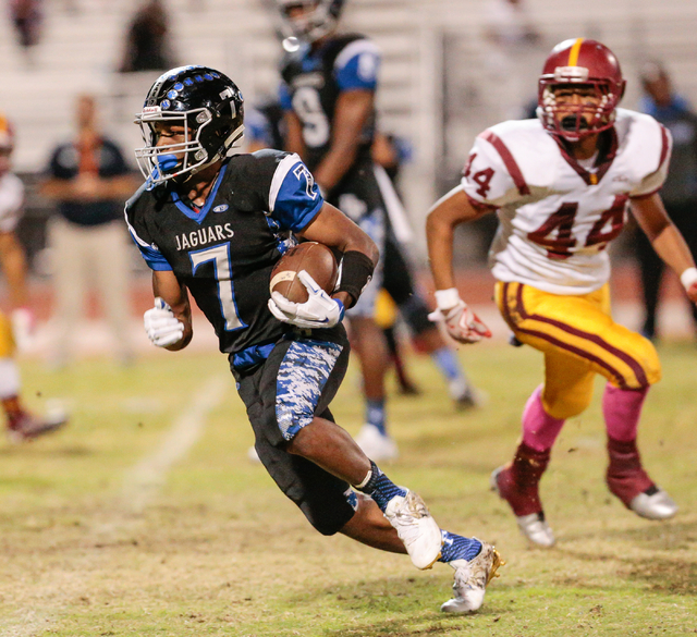 Desert Pines senior Isaiah Morris (7) runs the ball down the field as Del Sol sophomore Ati Poni (44) runs after him during the football Class 3A playoff game at Desert Pines High School in Las Ve ...