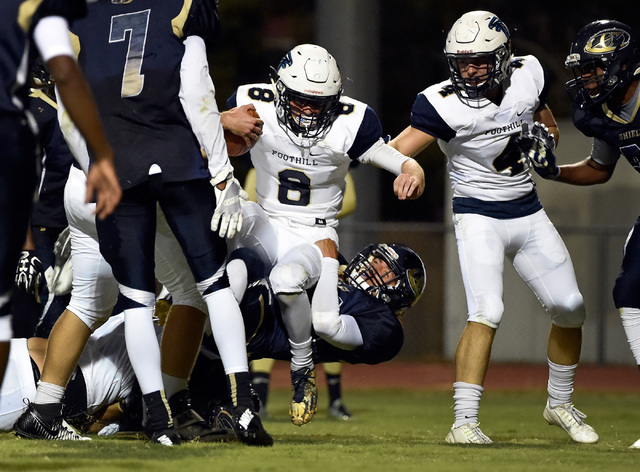 Foothill's Blake Wilson (8) crosses the goal line against Cheyenne's Joseph Kunicki for Foothill's second touchdown during the first half of a high school football game at Cheyenne High School in  ...