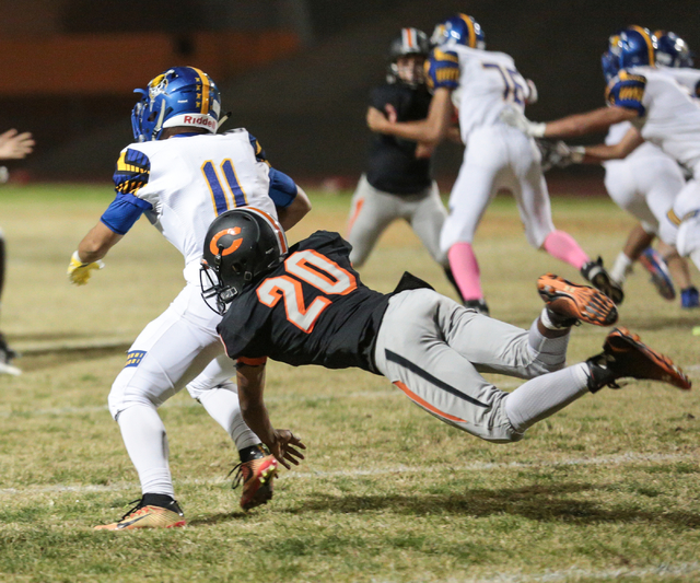 Chaparral  junior Dylan Disroe (20) attempts to bring down Moapa Valley sophomore Braeden St. John (11) during a football game at Chaparral High School in Las Vegas, Friday, Oct. 21, 2016. Donavon ...