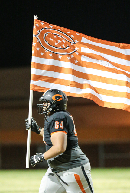 Chaparral senior Kalani Axtell-Lealao (64) runs down the field with the Cowboy's flag prior to the start of a football game against Moapa Valley held at Chaparral High School in Las Vegas, Friday, ...