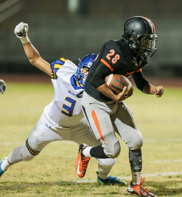 Moapa Valley sophomore Leo Rios (3) swings his arm in an attempt to grab Chaparral  junior Darius Disroe (28) during a football game at Chaparral High School in Las Vegas, Friday, Oct. 21, 2016. D ...
