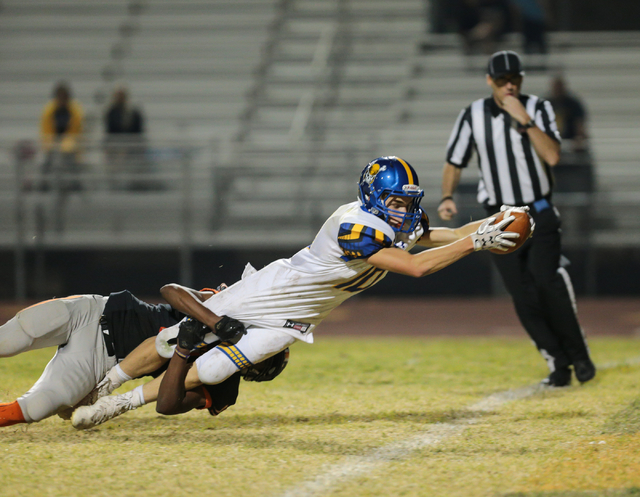 Moapa Valley senior Dayton Wolfley (10) stretches out with the ball over the goal line for a touchdown as he is brought down by Moapa Valley sophomore Braeden St. John (11) during a football game  ...