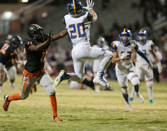 Moapa Valley senior Konner Andrew (20), right, jumps up for an interception in front of Chaparral senior Kentrell Petite (11) during a football game at Chaparral High School in Las Vegas, Friday,  ...