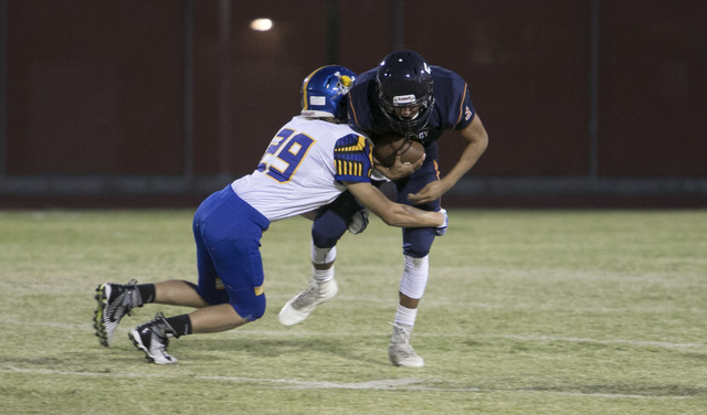 Legacy High quarterback Roberto Valenzuela, right, is brought down by Moapa Valley's Trent Barlow (29) during a varsity football game at Legacy High School on Friday, Sept. 9, 2016. Richard Brian/ ...