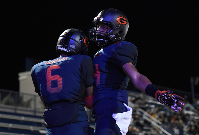Bishop Gorman's Austin Arnold (6) and Dorian Thompson-Robinson celebrate a touchdown against Palo Verde during the first half of a high school football game at Bishop Gorman High School, Thursday, ...