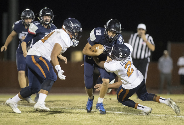 Quarterback Kody Presser (33) runs the ball through Legacy defenders DeAndre Caruthers (4) and Lamondrel Edmond (2) during a Legacy High School Shadow Ridge High School game at Legacy High School  ...