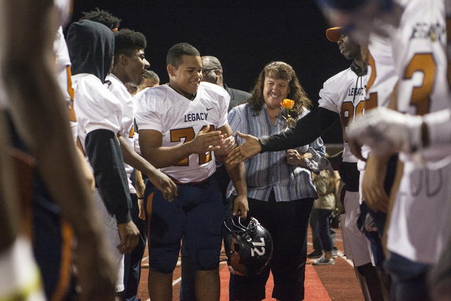 Noah Jefferson and his mom Dawn Jefferson are greeted by the other Legacy High School players before the Legacy High School Shadow Ridge High School game at Legacy High School in North Las Vegas o ...