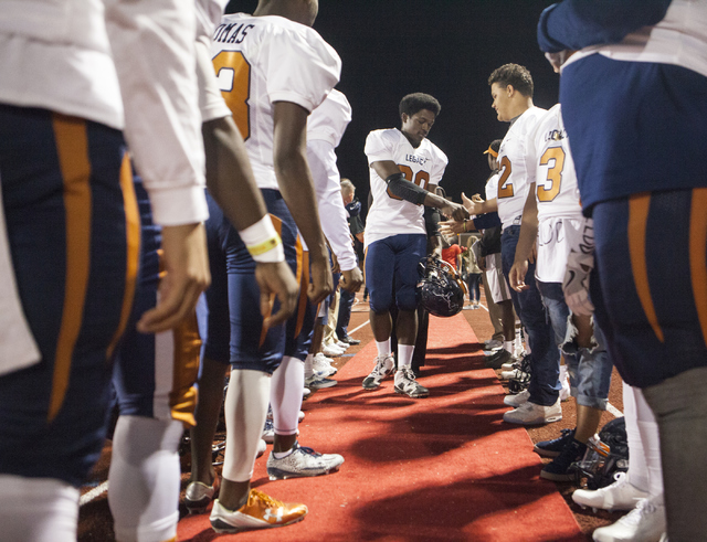 Christian Johnson is greeted by the other Legacy High School players before the Legacy High School Shadow Ridge High School game at Legacy High School in North Las Vegas on Friday, Nov. 4, 2016. L ...