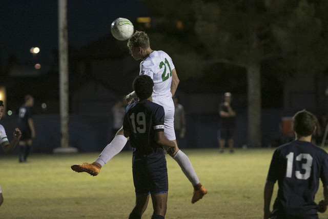 Green Valley forward Cole Aronson (21) connects with a header over Foothill's Kyle Thomas (19) during a varsity soccer game against Foothill at Green Valley High School on Thursday, Oct. 13, 2016. ...
