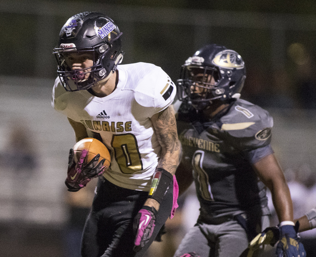 Sunrise Mountain High School's Daltyn Pytrysson (10) runs the ball against Cheyenne High School's Cameron Myles (1) during a football game at Cheyenne High School in North Las Vegas on Friday, Oct ...