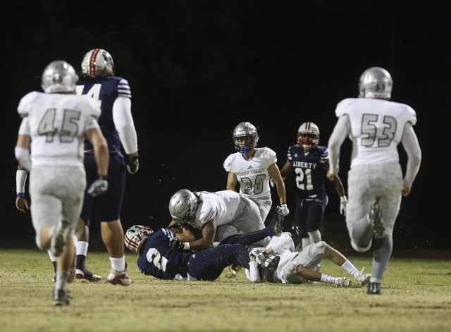 Liberty wide receiver Ethan Dedeaux (2) is taken down by Green Valley linebacker C.J. Araujo (2) during a football game at Liberty High School in Henderson on Friday, Sept. 30, 2016. Miranda Alam/ ...