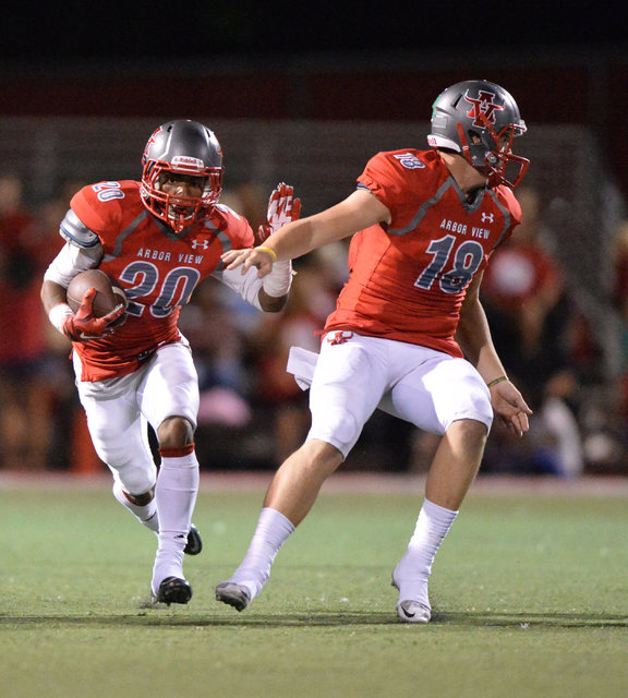 Arbor View running back Jaquari Hannie (20) runs the ball past quarterback Hayden Bollinger (18) during the Arbor View High School Shadow Ridge High School game at Arbor View in Las Vegas is seen  ...