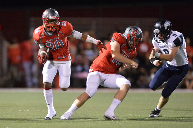 Arbor View quarterback Hayden Bollinger (18) blocks for running back Jaquari Hannie (20) during the Arbor View High School Shadow Ridge High School game at Arbor View in Las Vegas is seen on Frida ...