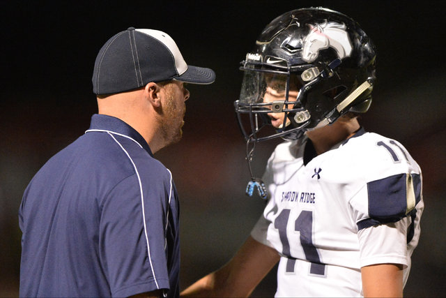 Shadow Ridge head coach Travis Foster talks to quarterback Travis Boston (11) during the Arbor View High School Shadow Ridge High School game at Arbor View in Las Vegas is seen on Friday, Sept. 30 ...