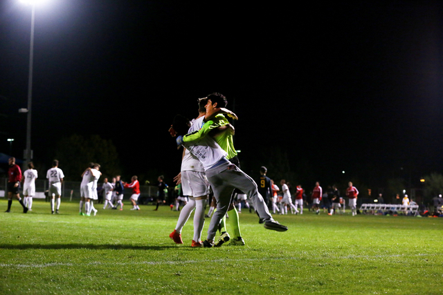 Coronado Cougars soccer team goalkeeper, Harrison Skinner, is hugged by teammates at the Bettye Wilson Soccer complex after the Cougars won the neutral playoff game against the Durango Trailblazer ...